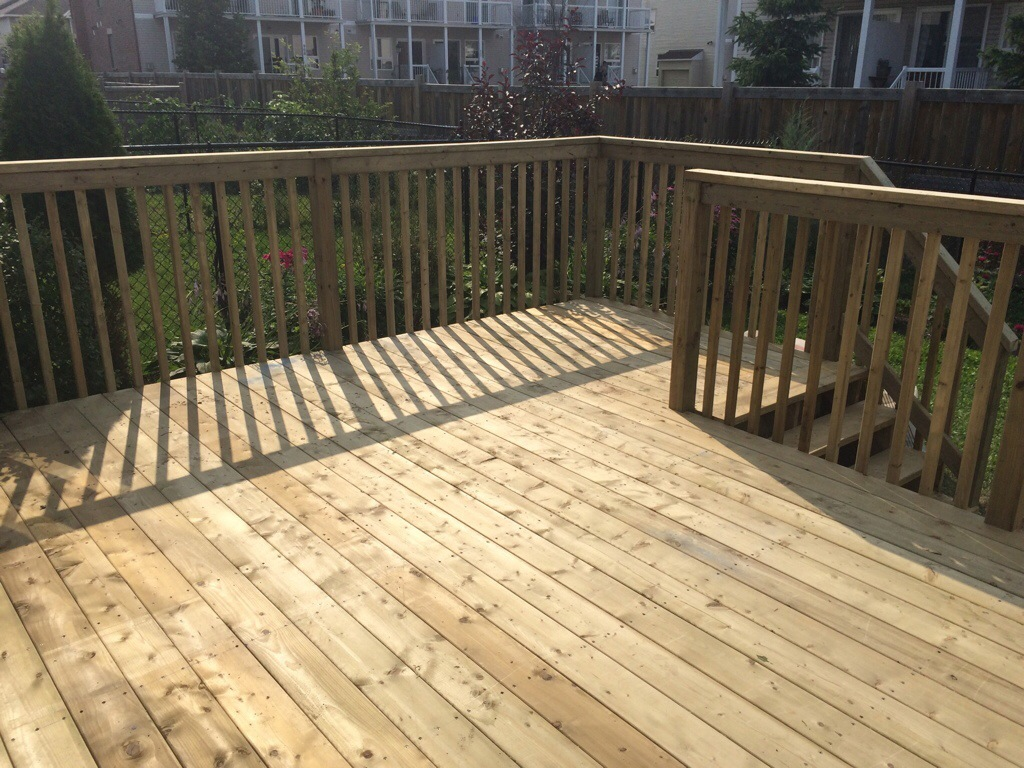 A backyard deck with rails and stairs.