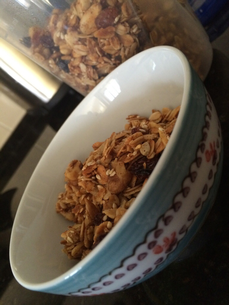 granola in a decorative cereal bowl with a container of granola behind