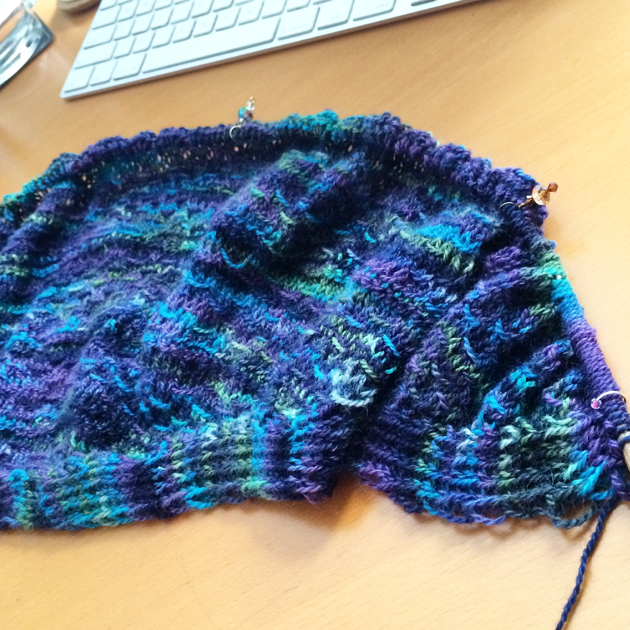 A partially knit blue variegated shawl on the needles.