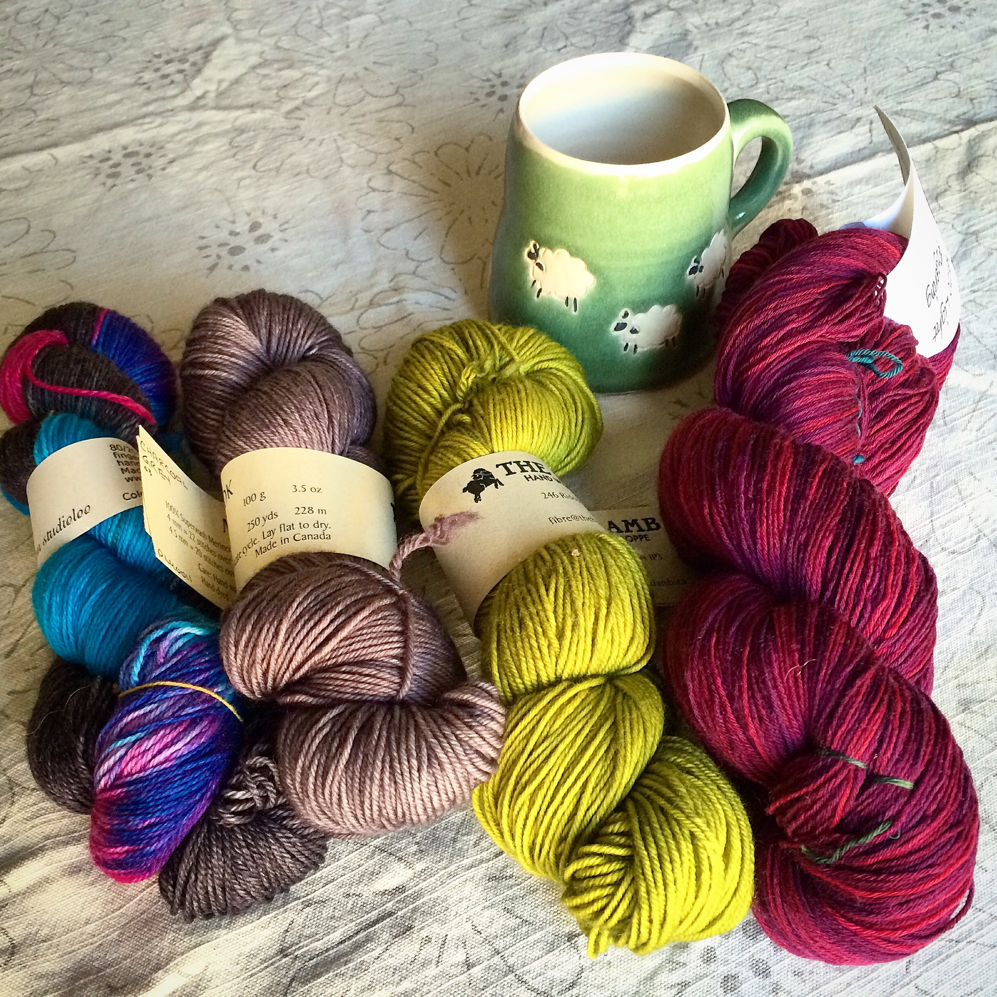 4 skeins of yarn and a hand-crafted mug